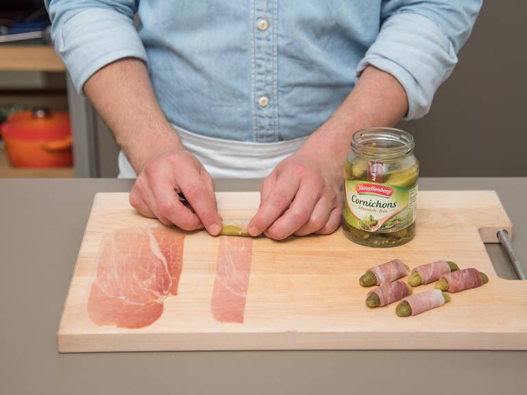 Cornichons halbieren. Parmaschinken ebenfalls längs halbieren. Jede Cornichonhälfte mit einem Streifen Parmaschinken umwickeln.