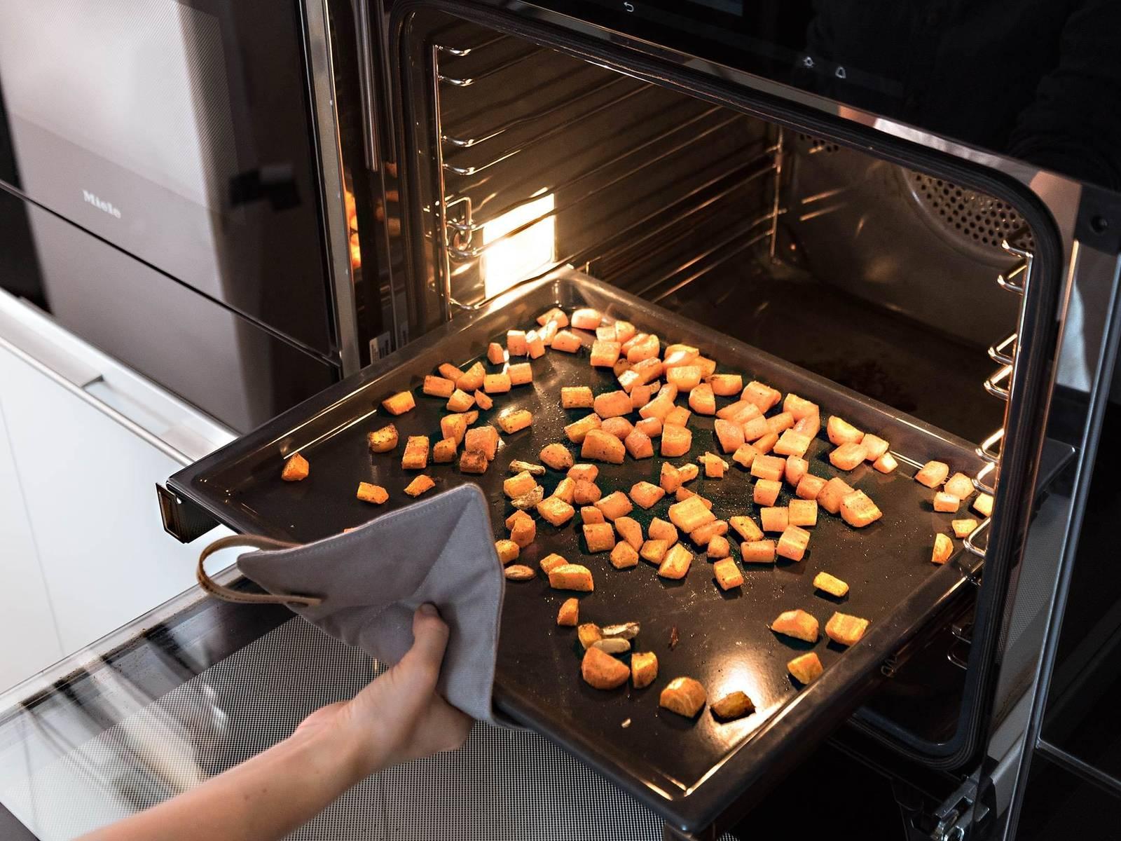 将胡萝卜混合物倒入烤盘中,放进烤箱,以200℃烤20分钟,直至胡萝卜变软。