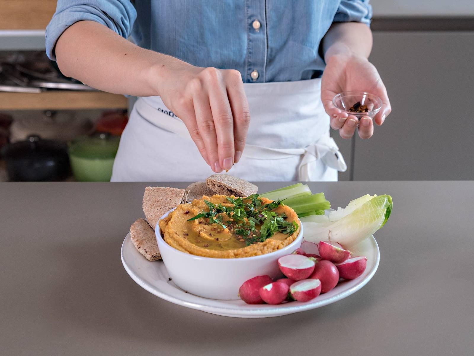 将鹰嘴豆泥放到上菜碗中,淋上橄榄油,撒辣椒粉和摩洛哥综合香料调味。将皮塔饼切成三角形,烤一烤,佐以鹰嘴豆泥享用!