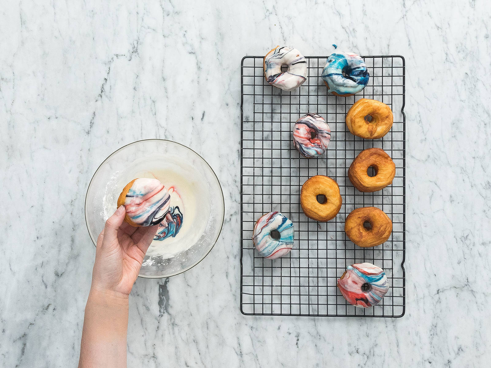In a large bowl, mix the confectioner's sugar, cream, vanilla extract, and salt. Add the food coloring and swirl to make a pattern as desired. Dip the top side of the donut into the icing and place it bottom side-down on a wire rack to set. Sprinkle edible glitter over them and enjoy!