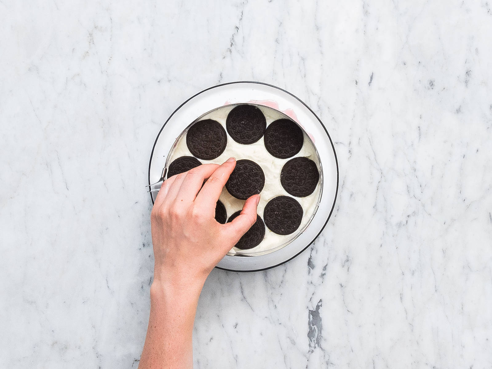 Place the cake ring on a cake plate and begin to assemble the cake. First, add a layer of cookies, then the pink cream, cookies, white cream. Repeat until all is used up. Use a rubber spatula to even out the layers. Place in the freezer to chill for approx. 8 hrs.