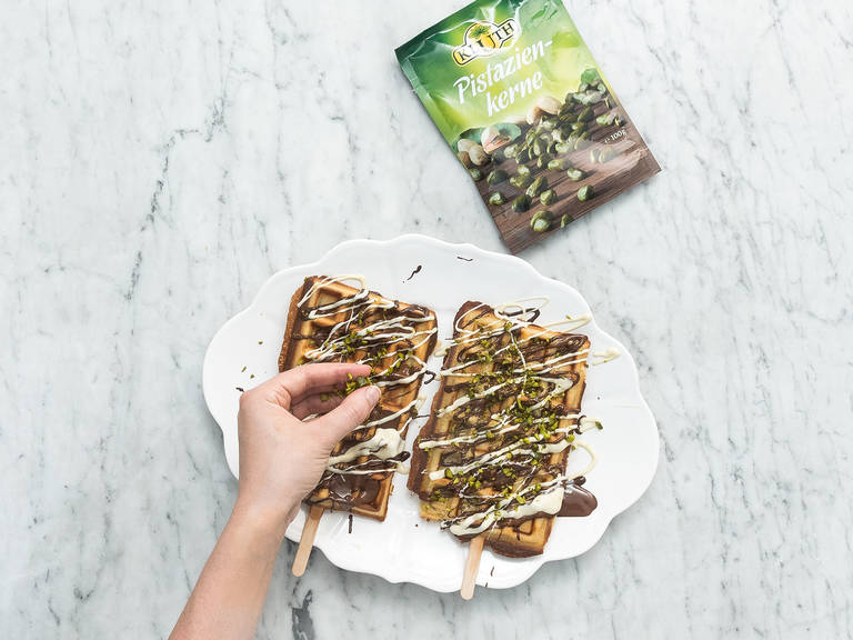 Drizzle a mixture of the  melted chocolate over baked waffles and sprinkle with chopped pistachios. Enjoy!