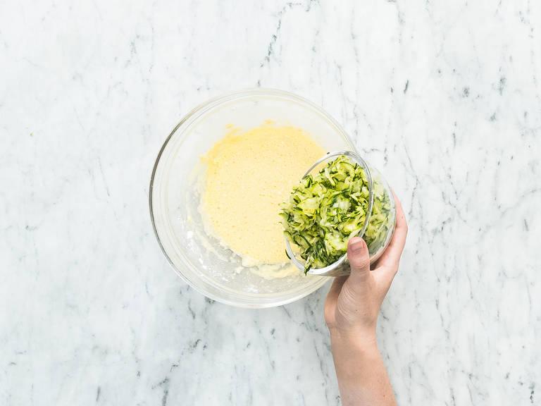 将鸡蛋、面粉和一撮糖放到搅拌碗中,搅拌均匀。倒入西葫芦丝中,裹匀。