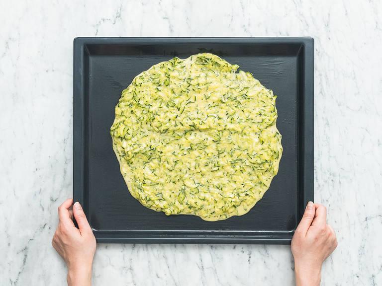 用橄榄油润滑烤盘,铺上西葫芦混合物。放入烤箱,以200℃烤25分钟,直至西葫芦变得金黄焦脆。