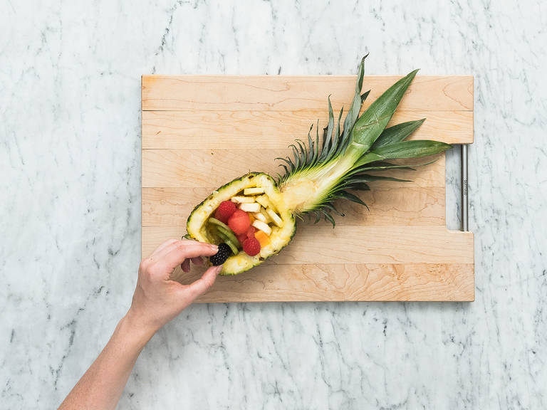 Arrange sliced fruit equally in both pineapple halves. Drizzle orange dressing on top and garnish with coconut flakes. Serve with Greek yogurt. Enjoy!