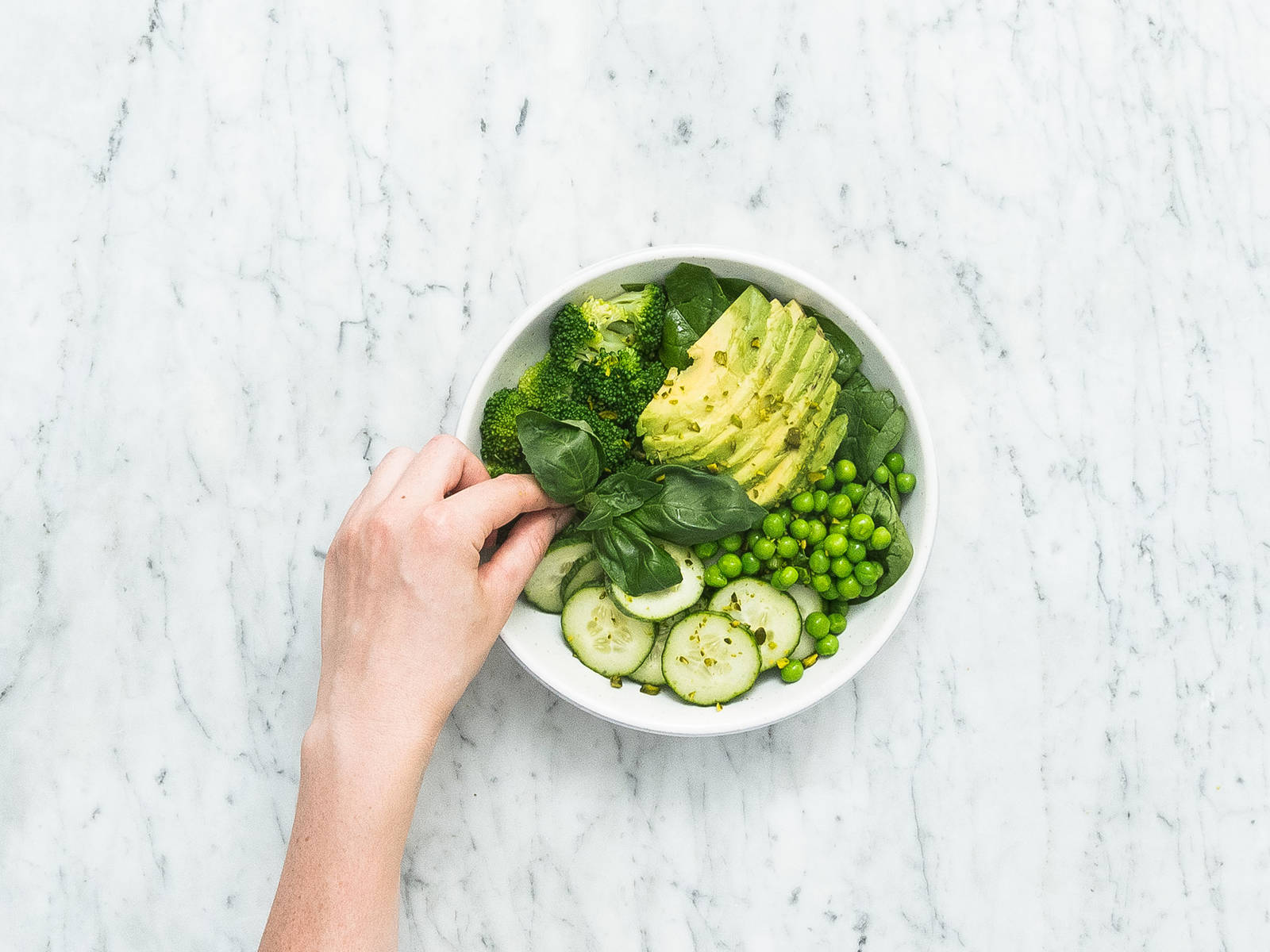 Arrange spinach, broccoli, cucumber, peas, and avocado in bowls. Garnish with basil and chopped pistachios and drizzle avocado dressing on top. Enjoy!