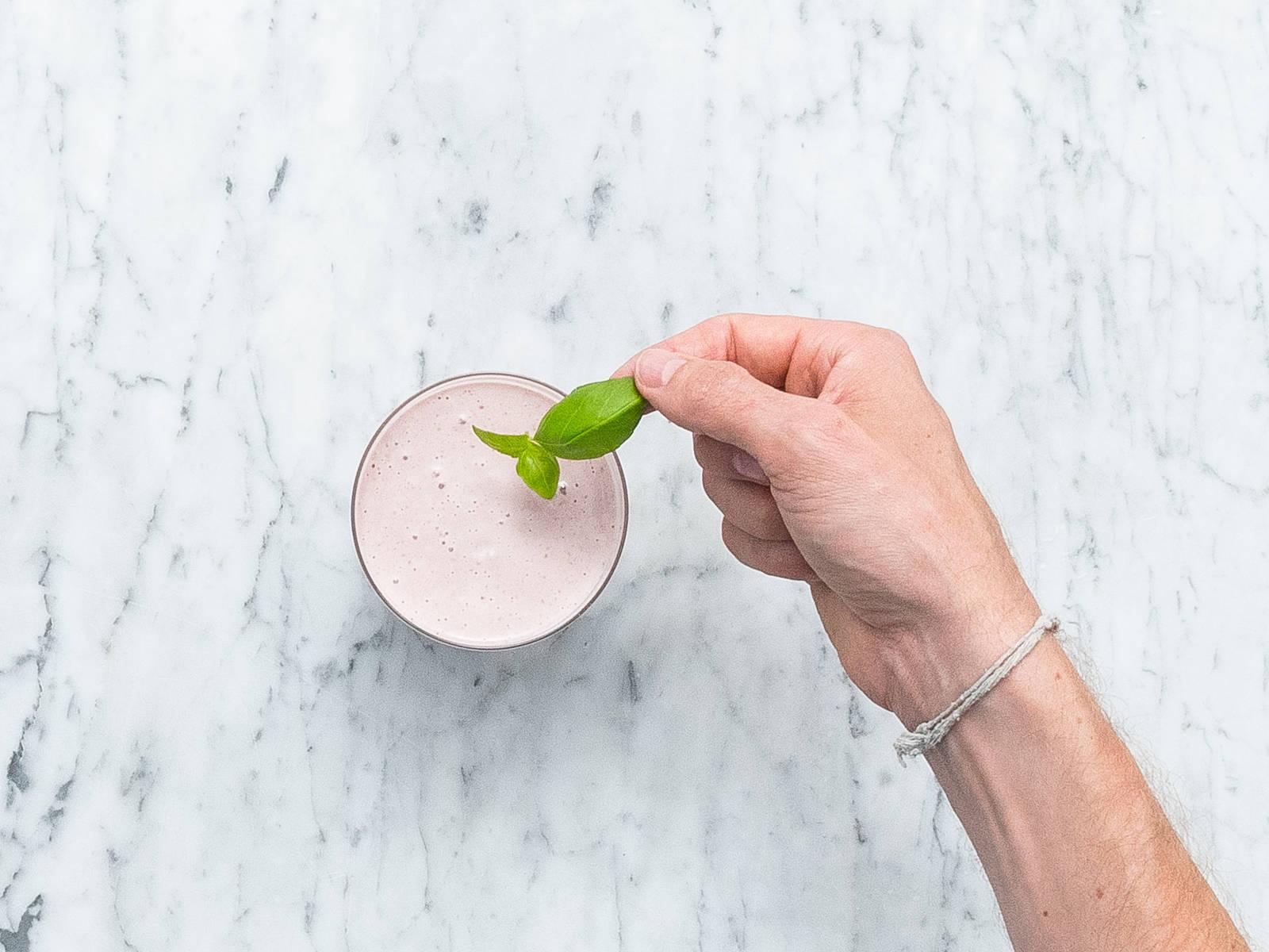 清洗草莓后摘去顶部叶片,切成四瓣。将奶昔倒入杯中,饰以罗勒叶和草莓。尽情享用吧!
