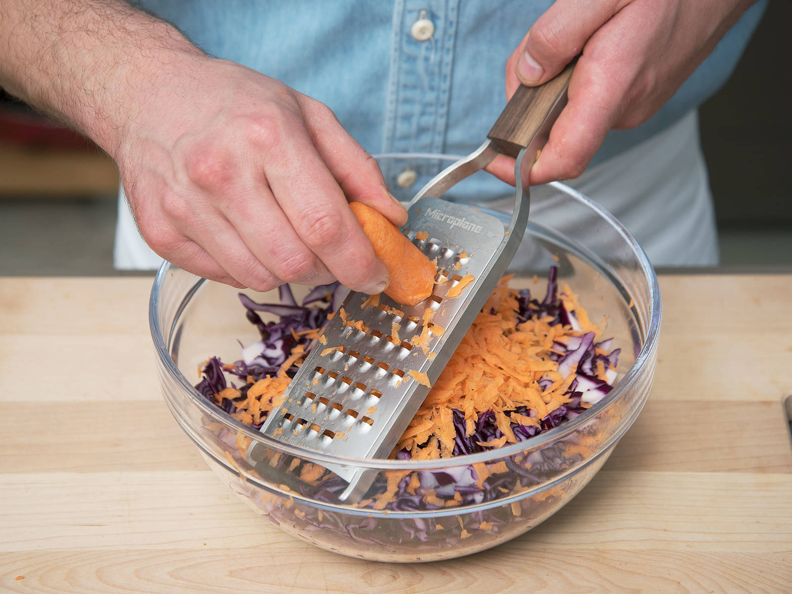Remove stem and outer leaves from the red cabbage. Roughly cut and grate it into a large bowl. Wash and grate carrots, then add them to the red cabbage.