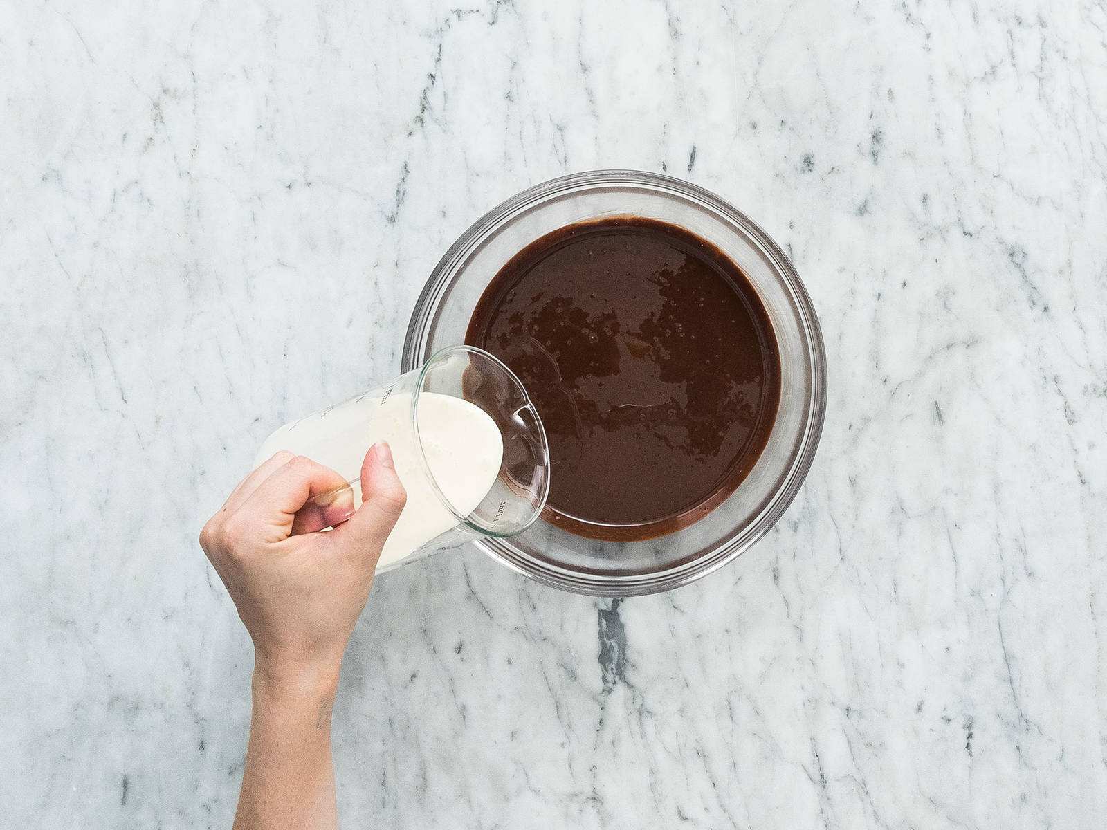 Add dark couverture chocolate to a mixing bowl and melt in a microwave, then add coconut oil and heavy cream. Stir until combined and let cool for approx. 5 – 10 min.