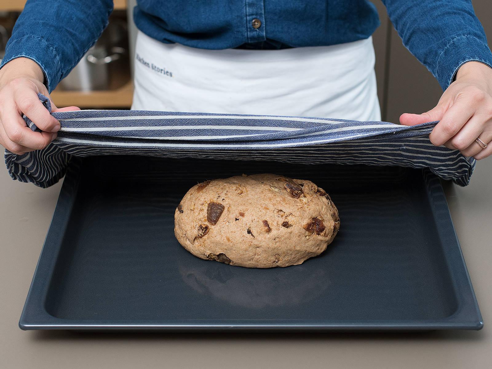 如有需要,在烤盘中铺好烘焙纸。将面团放到撒好面粉的工作台上,轻压,以释放空气。将剩余的无花果和核桃放到面团上,揉至充分混合。将面团揉成球状,放到烤盘中,盖上湿厨房纸,静置发酵1小时。