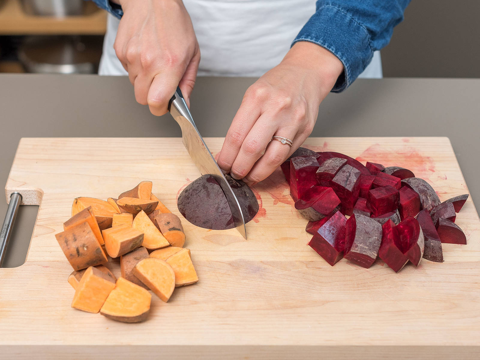 Backofen auf 220°C vorheizen. Süßkartoffeln und Rote Bete waschen und trocken tupfen. Rote Bete und Süßkartoffeln zunächst halbieren und danach in Stückchen schneiden. Einen Teil des Knoblauchs schälen und hacken.