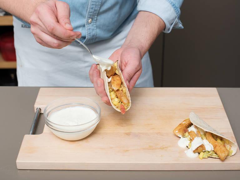 将部分法式酸奶油混合物抹到玉米饼上。在每片玉米饼上放些许炸鱼片,再淋上一些西柚萨萨酱。如果喜欢,可佐以青柠块。