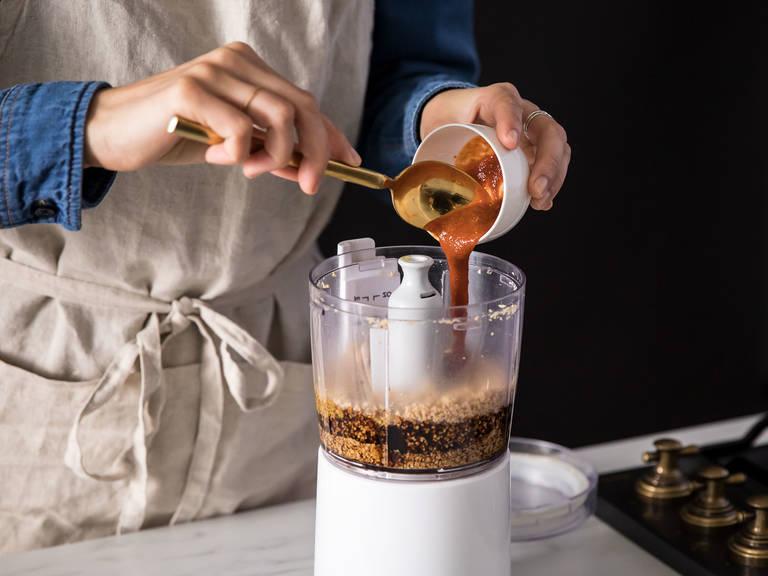 Den Großteil der gerösteten Erdnüsse in einem Zerkleinerer zu einer glatten Paste verarbeiten. Sojasauce, Sriracha, Wasser und Olivenöl dazugeben und zu einer cremigen Soße vermengen. Falls nötig, mehr Wasser dazugeben, damit die Soße dünn genug ist, um die Sobanudeln zu bedecken.