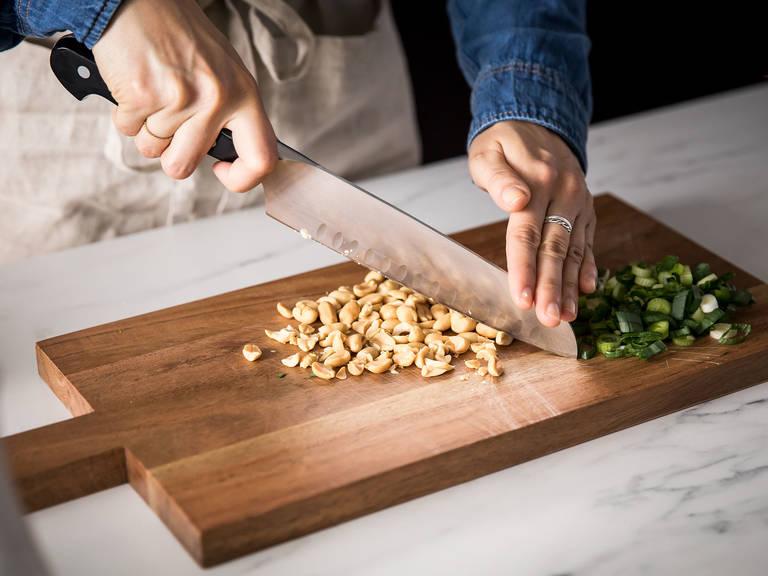 Restliche geröstete Erdnüsse hacken und Frühlingszwiebel in feine Ringe schneiden.