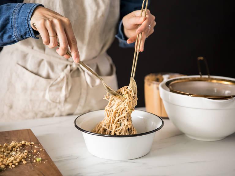 Sobanudeln und Erdnusssoße vermengen und in Servierschüsseln anrichten. Mit gehackten Erdnüssen und Frühlingszwiebel bestreuen. Mit Pfeffer abschmecken. Guten Appetit!
