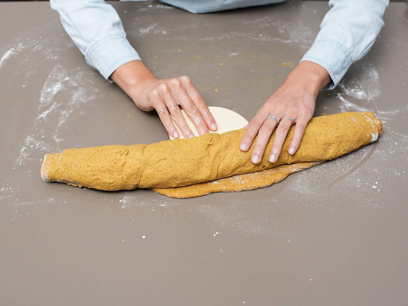 Den Teig von der langen Seiten beginnend fest einrollen, anschließend in zwölf gleich große Stücke schneiden. Die Kürbis-Zimtschnecken mit etwas Abstand voneinander in der Springform verteilen und nochmals ca. 40 Min. gehen lassen. Währenddessen den Backofen auf 180°C vorheizen.