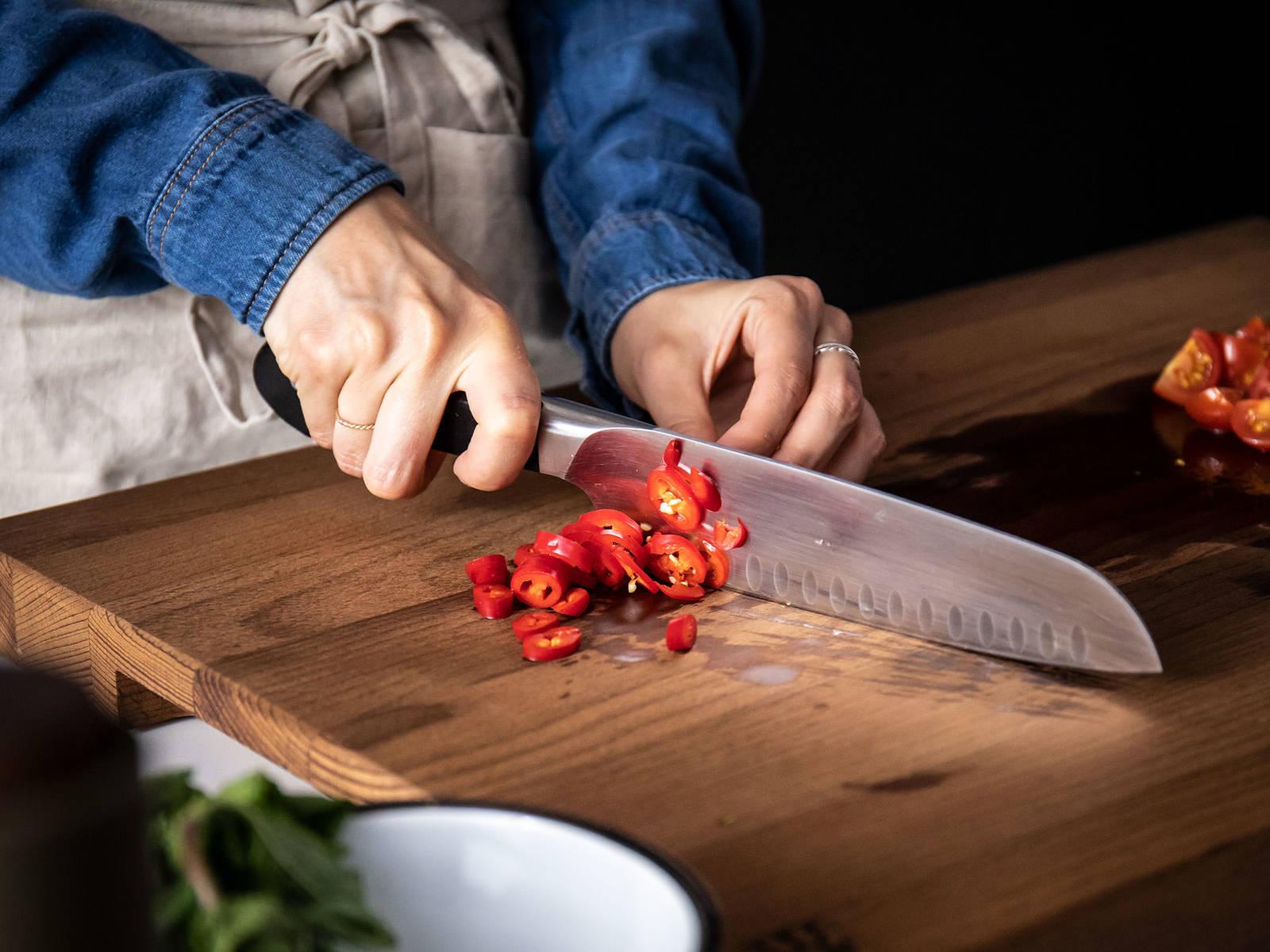 与此同时,樱桃番茄切四瓣,尖椒切细圈。摘下薄荷叶。一半放置一旁,用于装盘,另一半大略剁碎。当小茴香变透明时,放入樱桃番茄、尖椒、薄荷碎。在煮意面的同时,低火煸炒。