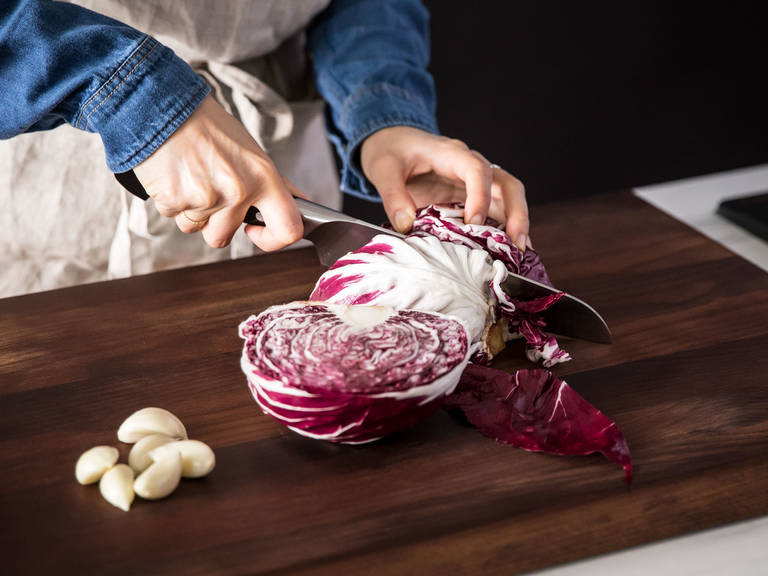 Hähnchenschenkel von beiden Seiten mit Salz und Pfeffer würzen. Den Strunk des Radicchios entfernen und in dünne Spalten schneiden. Knoblauchzehen schälen und zerdrücken.
