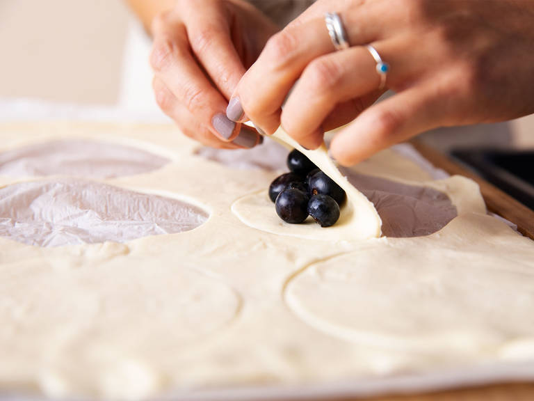Preheat oven to 210°C/410°F. Cut circles out of thawed puff pastry with a round cookie cutter. Lay fresh blueberries onto each circle and fold in half. Press the edges together with a fork to seal, and poke once or twice on top to make small holes for steam to escape. Transfer to a baking sheet and bake for approx. 10 min. or until golden brown.