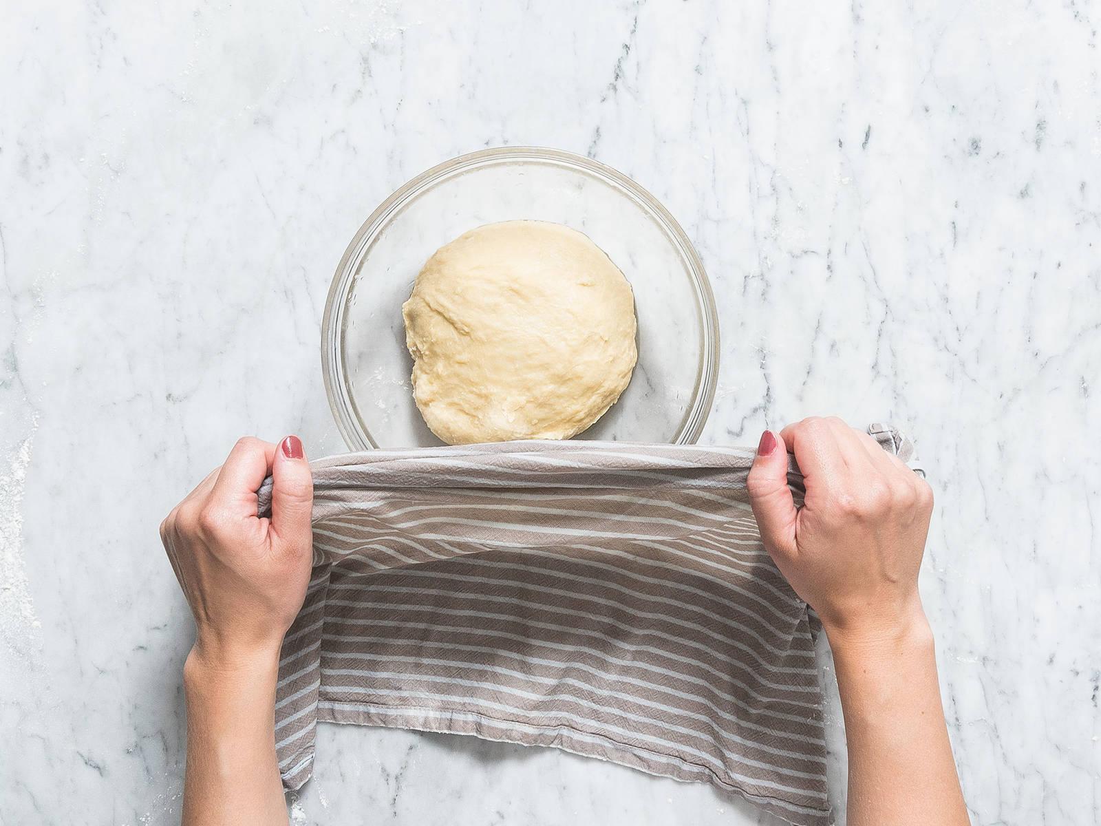 在一个大搅拌碗或搅拌机的碗中,混合面粉、盐和糖。酵母起泡之后,倒入面粉混合物中,然后倒入鸡蛋混合物,搅拌均匀。将面团放到撒了面粉的工作台上,揉面5-10分钟,如有需要可加入更多面粉,直至面团变软且有弹性(此时仍会有些粘手)。将面团放到油润滑过的碗中,盖上湿润的厨房毛巾,在室温中静置,直至面团膨胀至两倍体积,约需2小时。