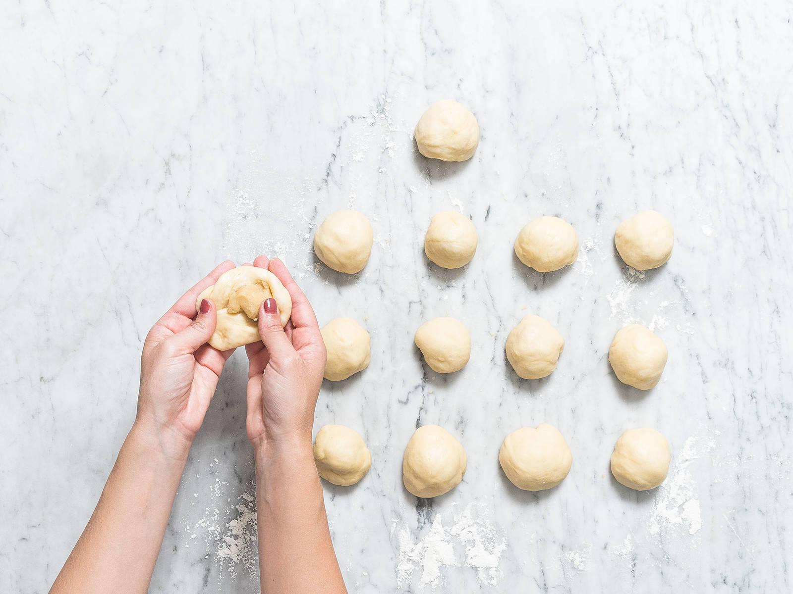 如有需要,可在两个烤盘中铺好烘焙纸,将烤箱预热至190℃。面团发酵好后,放到撒好面粉中的工作台上,分成多个小面球。稍微压平每个面球,在中间填入一汤匙杏仁蛋白软糖。密封好后,密封边朝下放到烤盘中,均匀放好,中间留下空隙。盖上湿润的厨房毛巾,静置发酵30分钟。