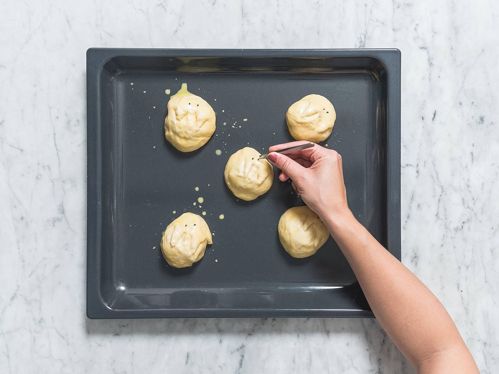 在一个小碗中,将预留的蛋黄加些许水搅打,刷到面团上。一次刷三个面团,以确保黑芝麻能好好黏在蛋黄上。用小钳子黏上黑芝麻做眼睛,用剪刀剪出两个1厘米的面团,作为耳朵。烤15-20分钟,或者烤至金黄。