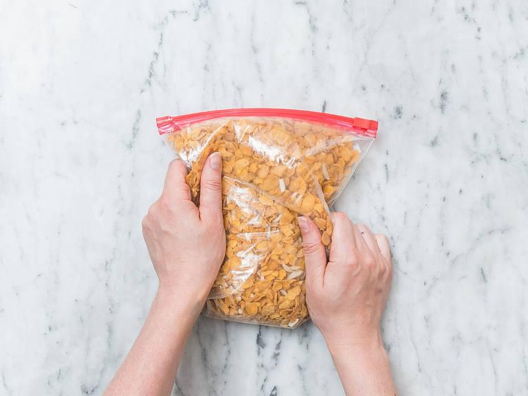 将玉米片和杏仁片放入密封袋中,用手或擀面杖碾碎。