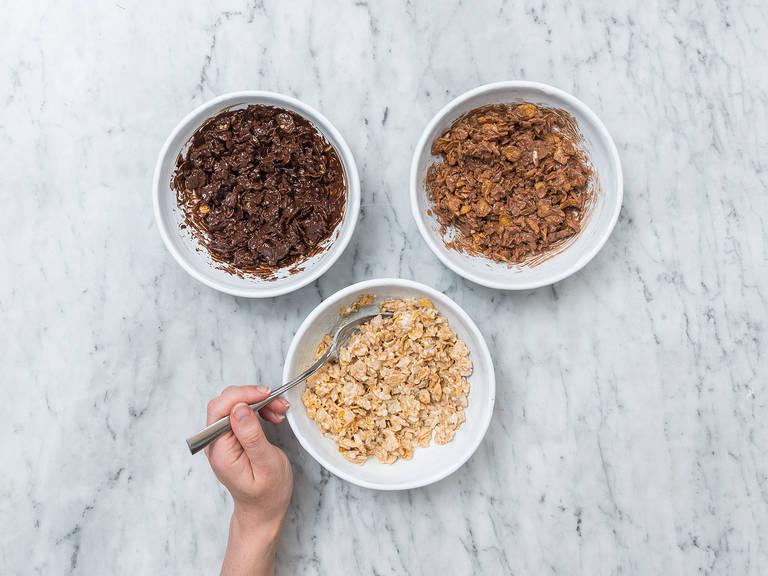 将各类巧克力分别放入三个碗中。一一进行隔水加热。轻轻搅拌至巧克力融化,然后稍微放凉。将玉米杏仁碎均匀分配到每个碗中,然后充分搅拌。
