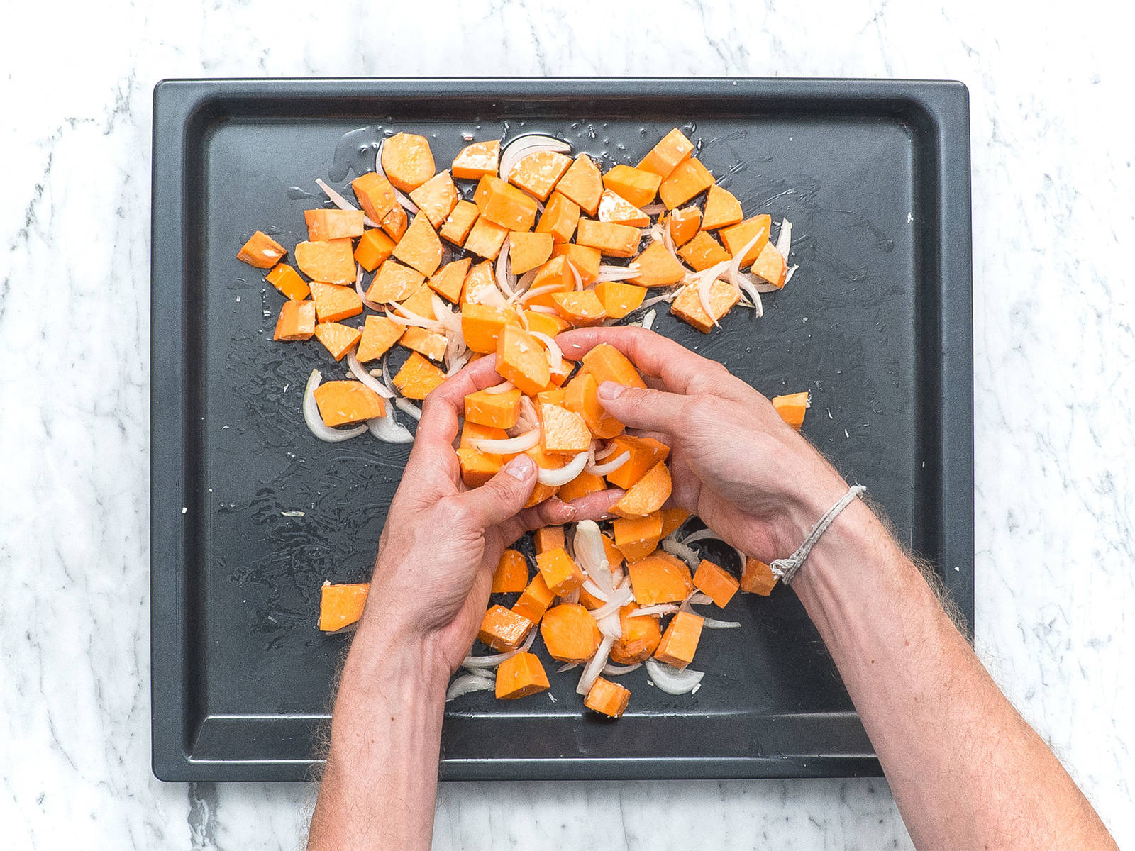Add sliced sweet potato, onion, shredded coconut, melted coconut oil, garlic, sea salt, and pepper to a baking sheet and toss to coat. Bake at 210°C/410°F for approx. 20 min. Then remove from the oven and let cool down a bit.
