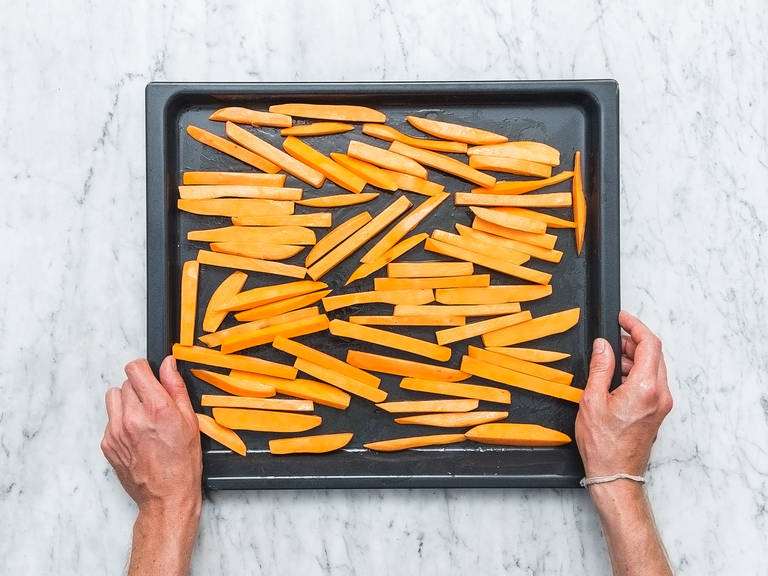 Pre-heat oven to 220°C/430°F. Cut sweet potatoes into matchsticks and transfer them to a large bowl. Add cornstarch and toss to coat. Spread sweet potato fries over a baking sheet. Add some oil and smoked ground paprika and toss to coat. Bake for approx. 20 min. or until golden-brown and crisp. Remove from oven and season with salt to taste.