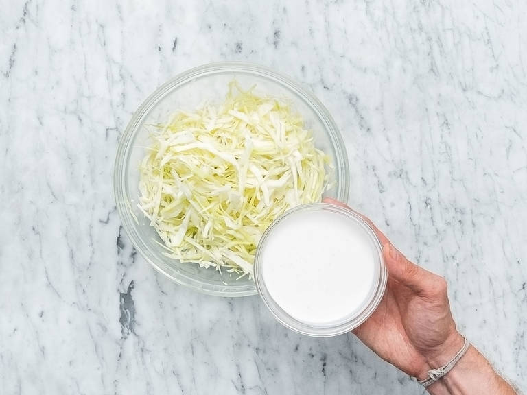 Finely slice white cabbage and transfer to a bowl. Add cashew cream, white balsamic vinegar, coriander, salt, and pepper, and stir to combine. Let sit until serving to marinate.