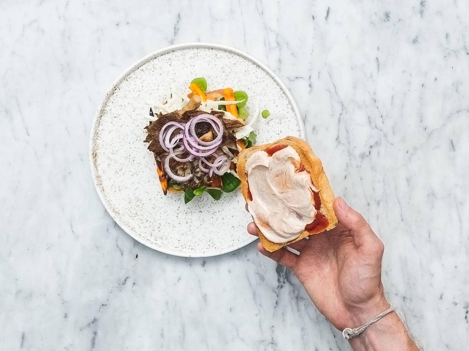 Ketchup und die vegane Chili-Zimt-Mayo auf den getoasteten Brotscheiben verteilen. Die Hälfte der Brotscheiben mit Feldsalat, Süßkartoffelpommes, Weißkraut, gebratenen Austernpilzen und einigen Zwiebelringen belegen. Die andere Hälfte der Brotscheiben darauf legen. Guten Appetit!
