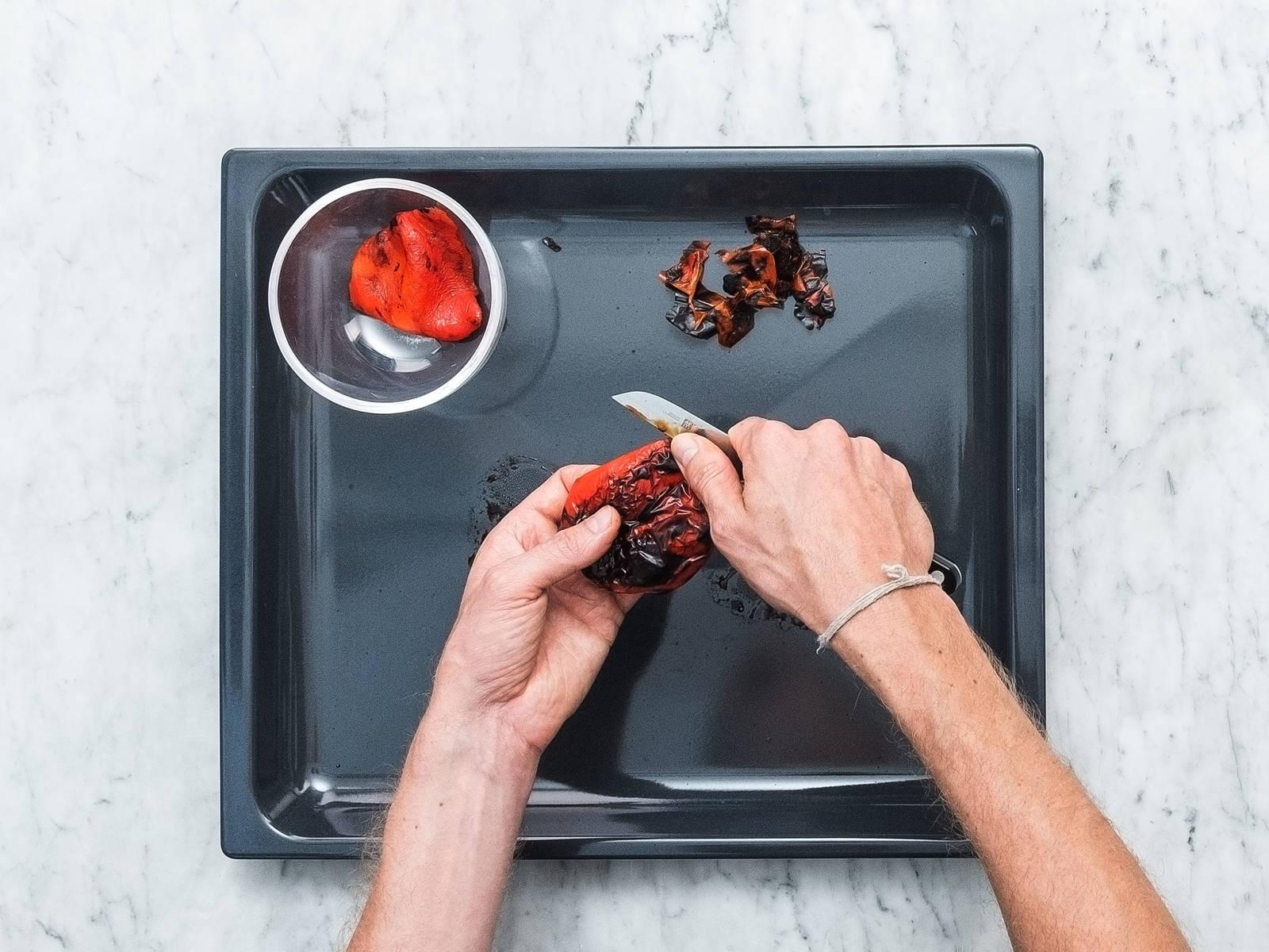 打开烤箱的烧烤功能,以最高火预热。将灯笼椒切半,去籽,并清洗。将灯笼椒的外部一面朝上,放到烤盘上,以高温烤10分钟,直至其外皮完全变黑。从烤箱中取出,盖上微湿厨房纸,放凉。用刀刮去灯笼椒烧黑的外皮,弃用。
