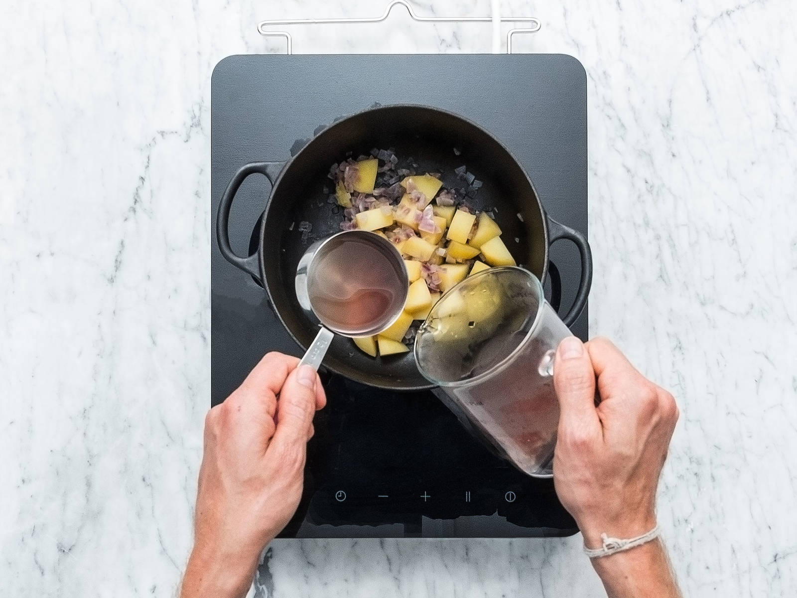 将洋葱和土豆去皮后切丁,然后倒入锅中,倒水没过,煮15分钟,将其煮软。留出一些煮菜水并捞出洋葱、土豆,置于一旁。