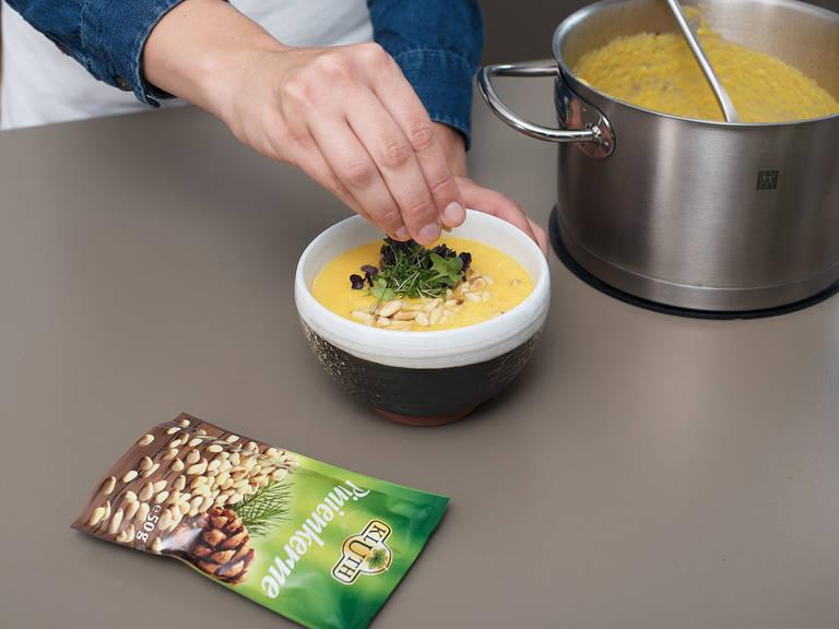 用手持搅拌机将汤搅打成泥。拌入法式酸奶油。与此同时,将松子放到煎锅中烘香。将汤倒入碗中,撒上松子,饰以小片绿叶菜。尽情享用吧!