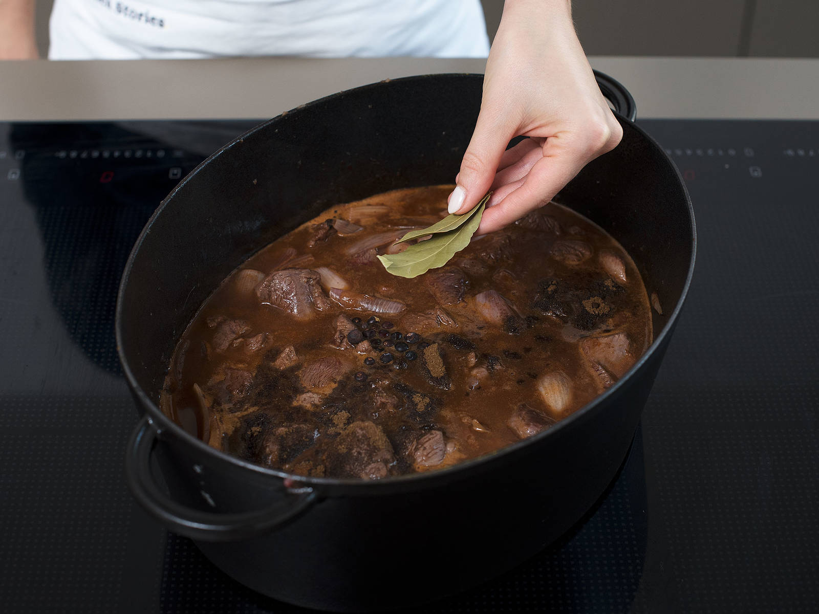 Add beef stock, juniper berries, bay leaves, and venison spice to the pot, and leave to simmer on low heat for approx. 1.5 hrs., stirring occasionally. Remove juniper berries and bay leaves. Add chanterelles and let simmer for another 15 min. Add salt and pepper to taste. Garnish with chopped parsley and crème fraîche. Serve with juniper berry marmalade and semolina dumplings. Enjoy!