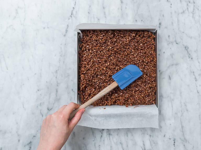 Puffreis in eine Schüssel geben und beiseitestellen. Vollmilchschokolade in eine hitzebeständige Schüssel geben und über einem Topf mit köchelndem Wasser schmelzen lassen. Die Schokolade dabei gelegentlich umrühren. Vom Herd nehmen und auf Raumtemperatur abkühlen lassen. Geschmolzene Schokolade zum Puffreis geben und vermengen. Backform mit Backpapier auslegen und die Puffreis-Masse einfüllen. Ca. 2 Stunden in den Kühlschrank stellen.