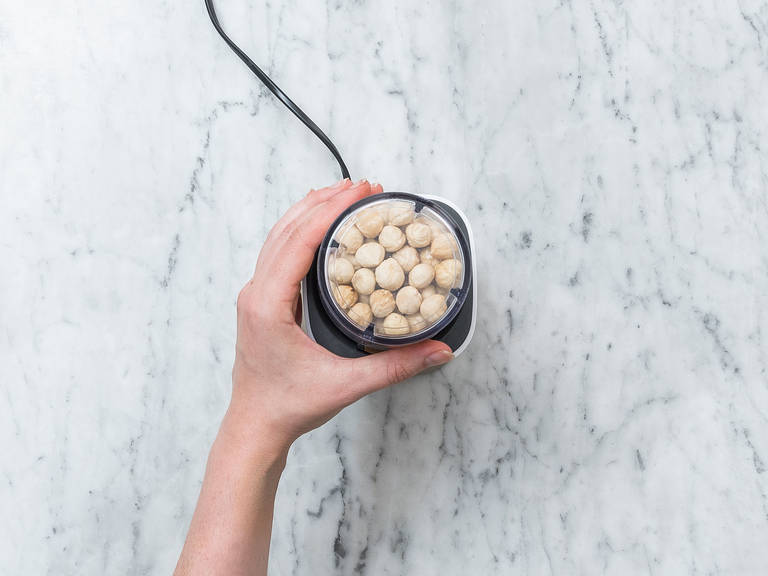 Toast hazelnuts in a frying pan set over medium heat for approx. 5 min. Transfer hot hazelnuts to a kitchen towel. Rub together to peel nuts. Transfer skinned hazelnuts to a food processor and blend for approx. 10 min., or until creamy.