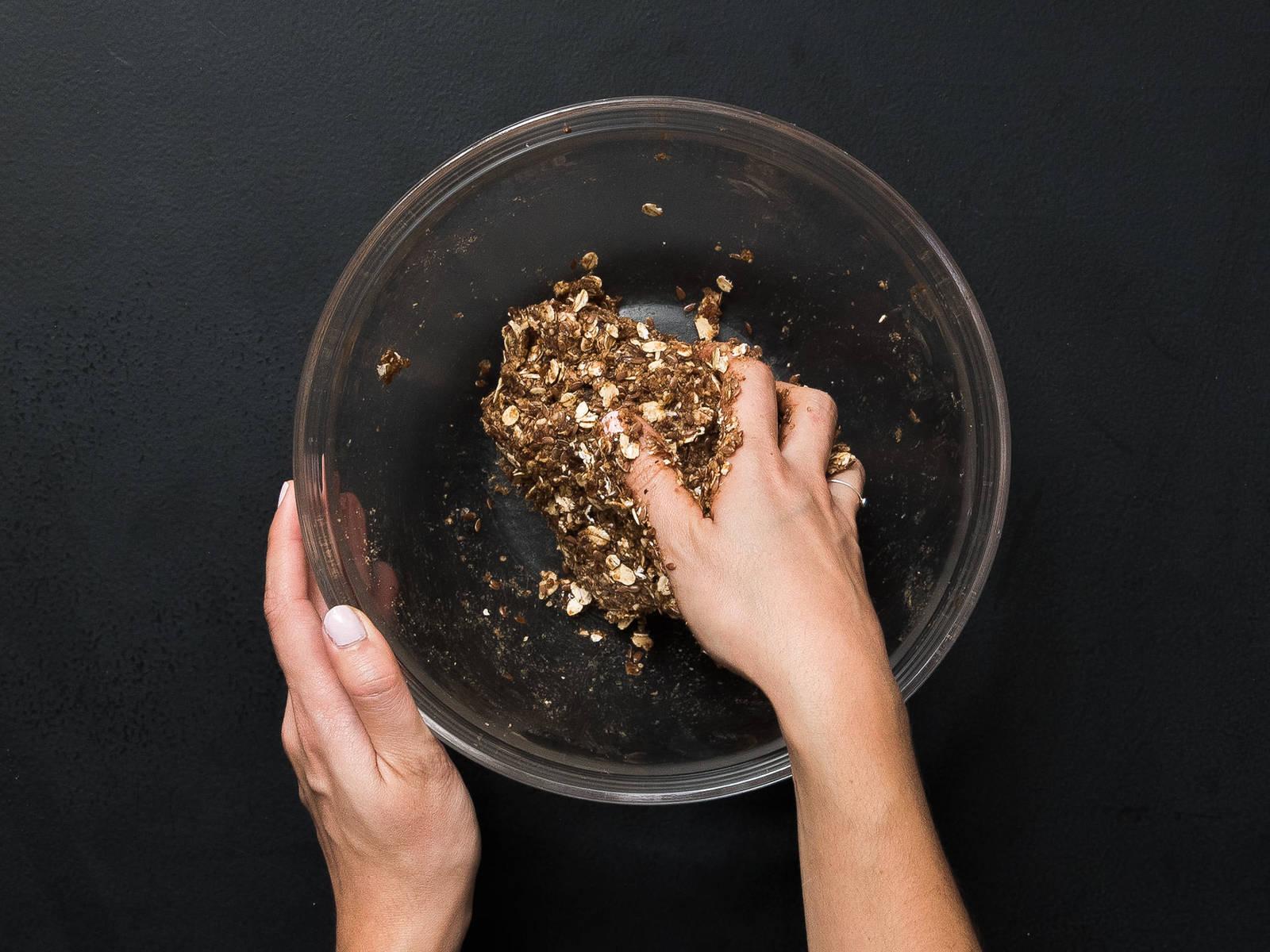 Die Hälfte der Haferflocken-Mischung, Datteln und Kokosöl in einen Zerkleinerer geben und mixen. Zurück zur restlichen Haferflocken-Mischung in die Schüssel geben und zu einen Teig verkneten.