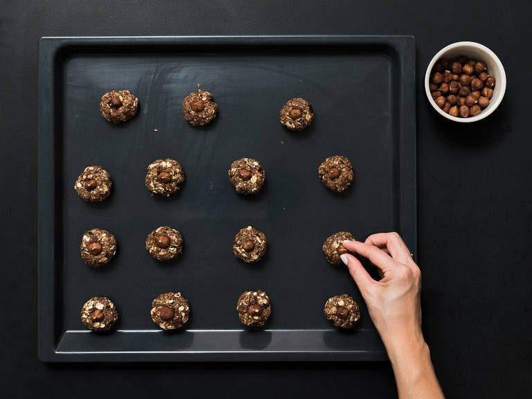 Form small balls of dough and place on a parchment-lined baking sheet. Lightly press 1 hazelnut into the top of each ball. Place in oven at 180°C/350°F and bake for approx. 15 min. Set aside to cool. Enjoy!
