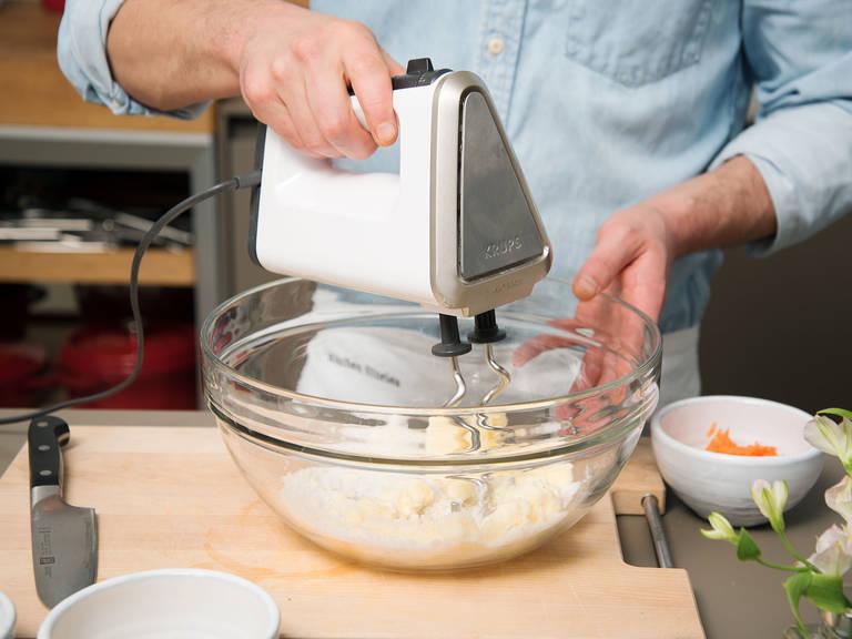 将软黄油、剩余的糖和些许盐放入另一碗中,搅拌混合。放入蛋黄、面粉、杏仁粉、胡萝卜丝、泡打粉、肉桂、些许柠檬汁和姜黄粉,再次搅拌均匀。拌入搅打好的蛋白,搅拌至形成光滑面糊。
