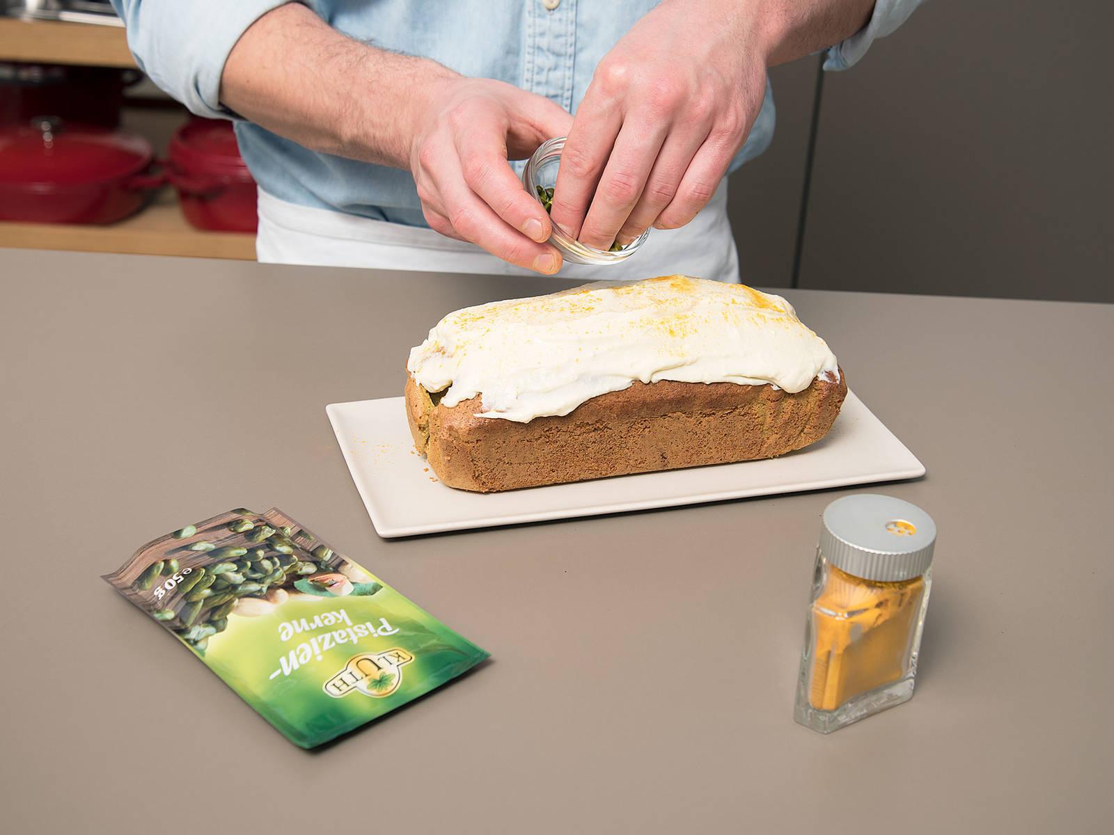 Während der Kuchen im Backofen ist, Frischkäse, Honig, restliches Salz, Zitronenabrieb und Zitronensaft in eine Schüssel geben und vermengen. Den ausgekühlen Kuchen mit der Frischkäse-Mischung bestreichen. Mit gemahlener Kurkuma und gehackten Pistazien bestreuen. Guten Appetit!