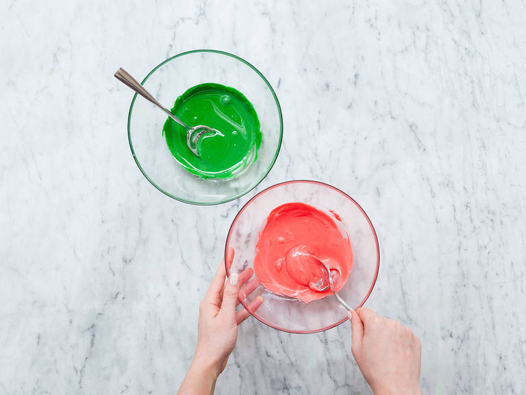 For the icing, add egg whites to a large mixing bowl. Sieve confectioner's sugar into the bowl, then beat until fluffy and stiff. Divide into three parts and add red and green food coloring to one part each. The third part stays white.