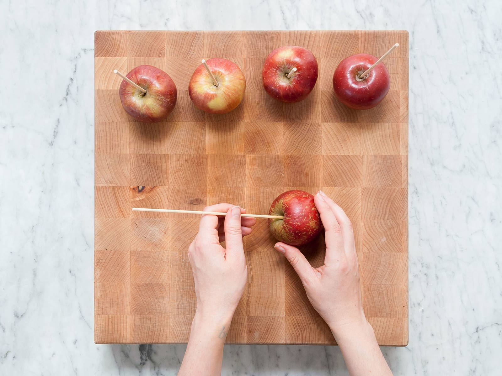 Wash apples, remove stems, and press a wooden skewers into each stem-end of the apples. Set aside.