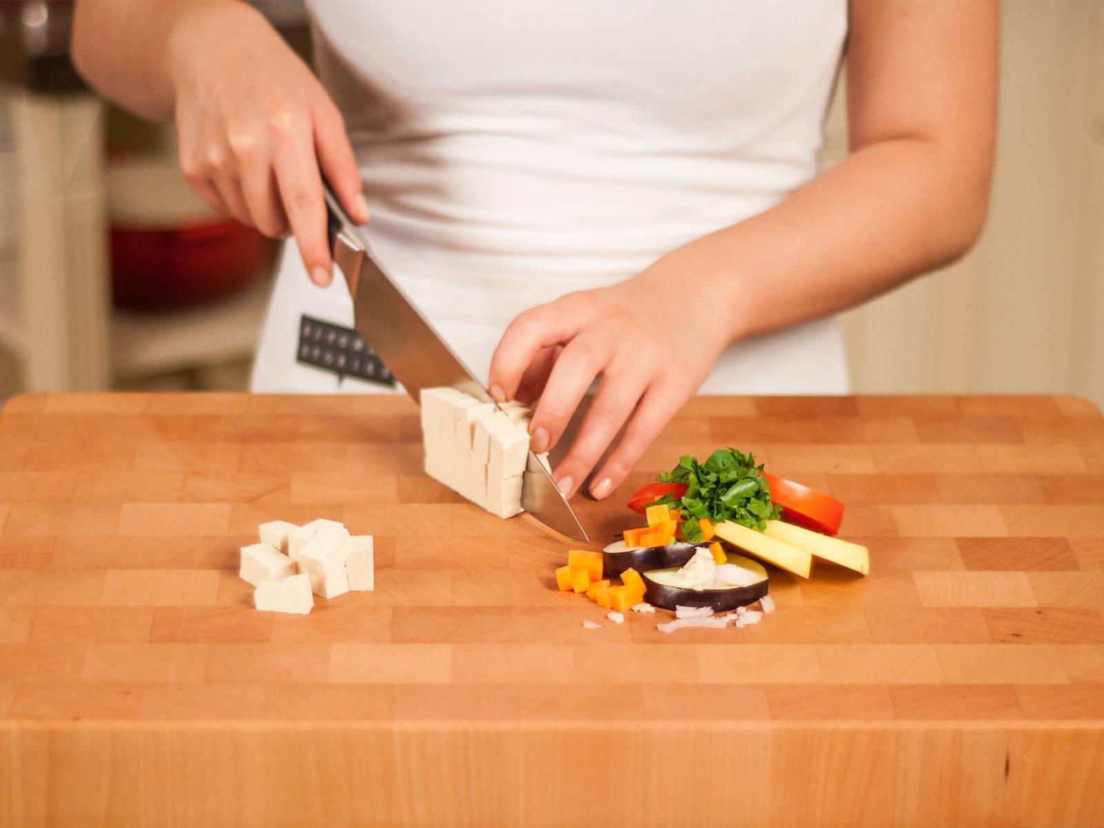 将土豆、茄子和番茄切成片。将红葱头和胡萝卜切成小丁,将大蒜剁成末,将欧芹粗粗剁碎,将豆腐切成小方块。