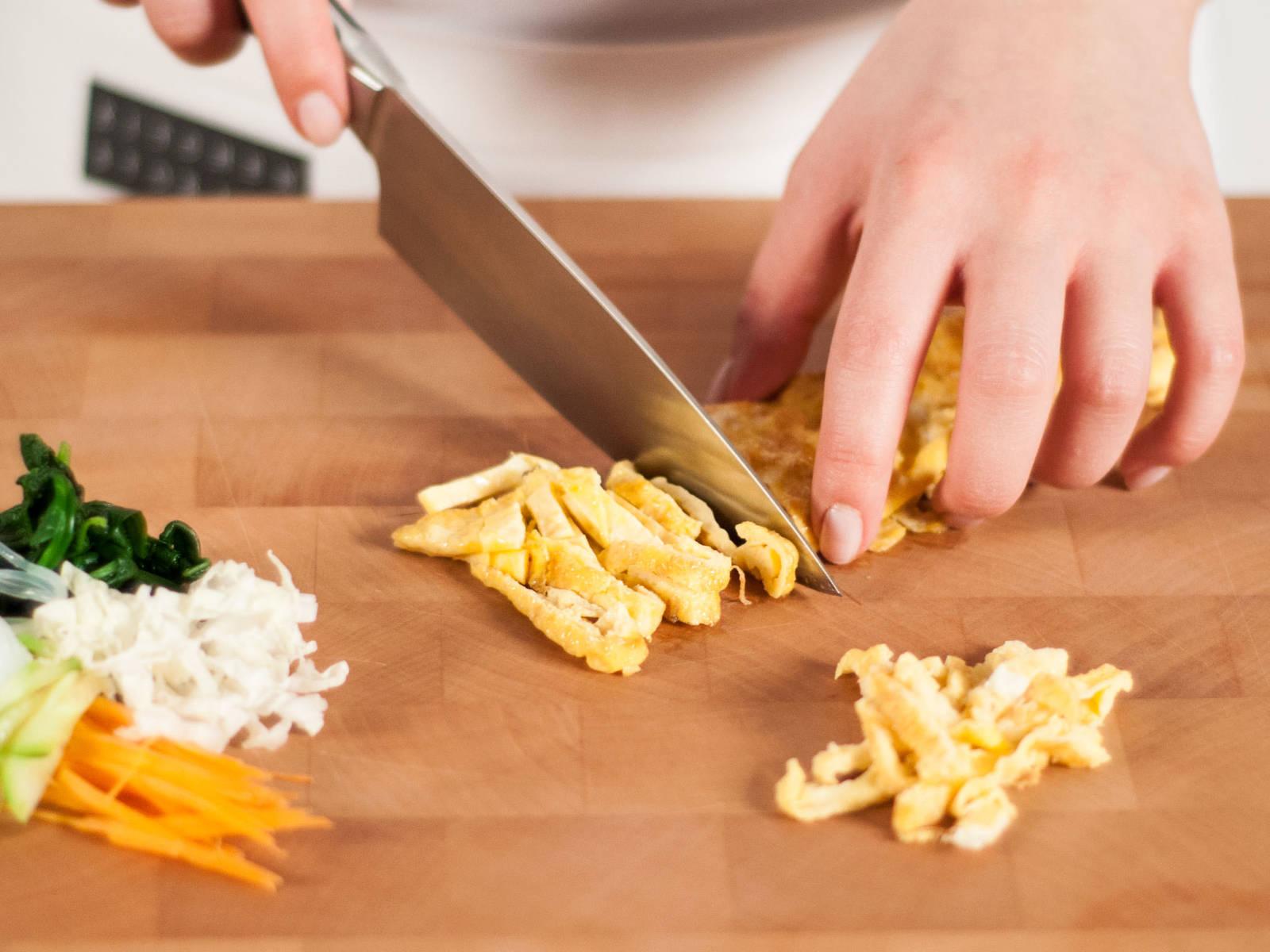 Spinat grob hacken. Knoblauch fein hacken. Karotte, Gurke, Chinakohl und die gebratenen Eier in feine Streifen schneiden.
