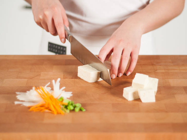 Cut daikons and carrot into fine strips. Finely slice spring onions, roughly chop the cilantro. Cut tofu into cubes.