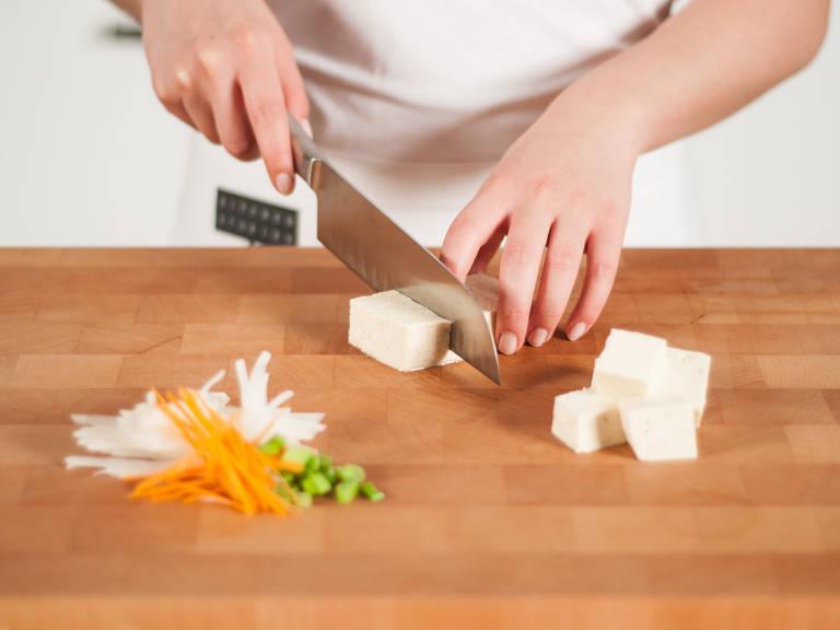 Rettiche und Karotten in feine Streifen schneiden. Frühlingszwiebeln fein schneiden, Koriander grob zerkleinern. Tofu in Würfel schneiden.