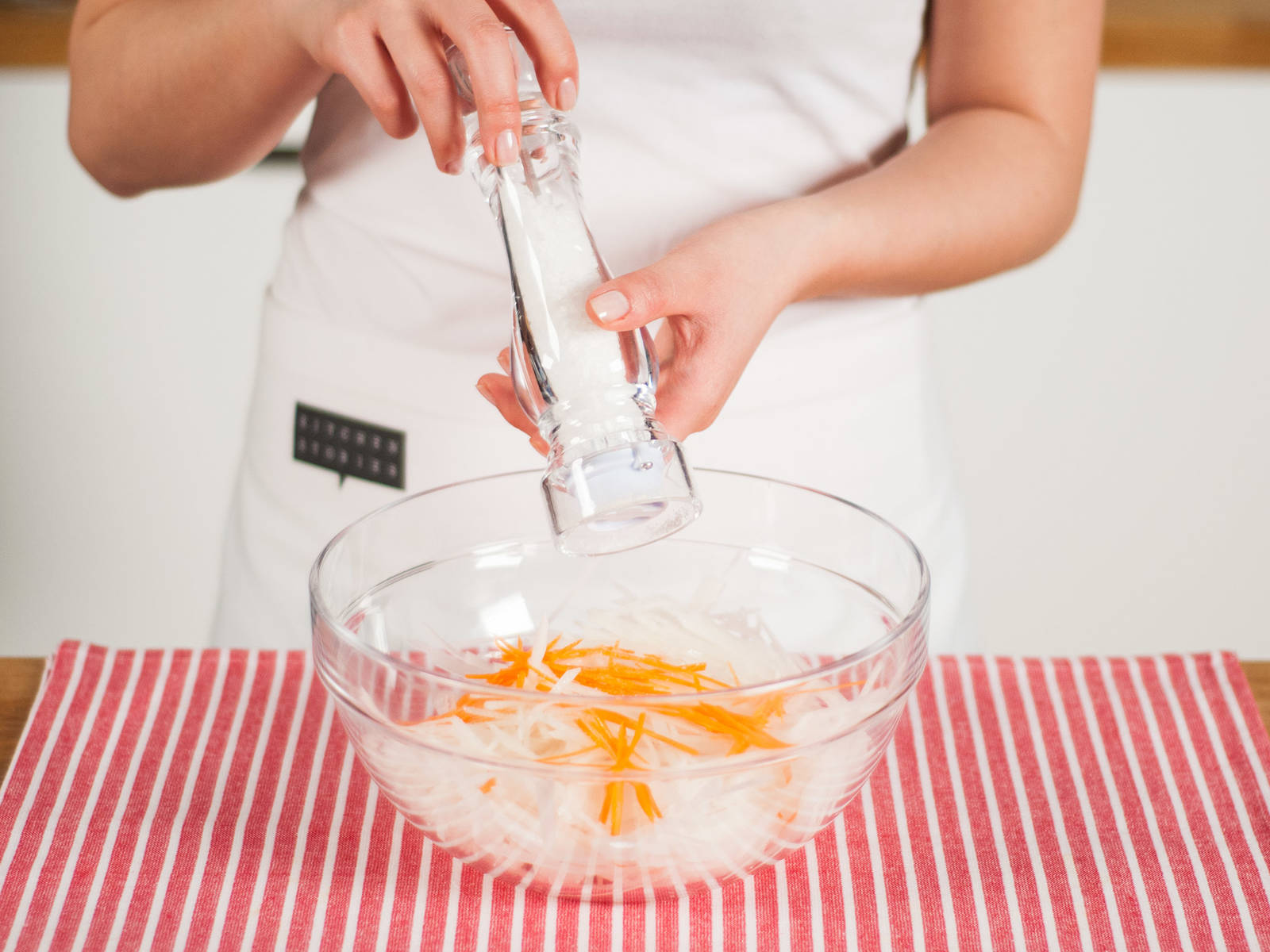 Karotten und Rettichstifte in eine große Schüssel geben. Mit Salz würzen.