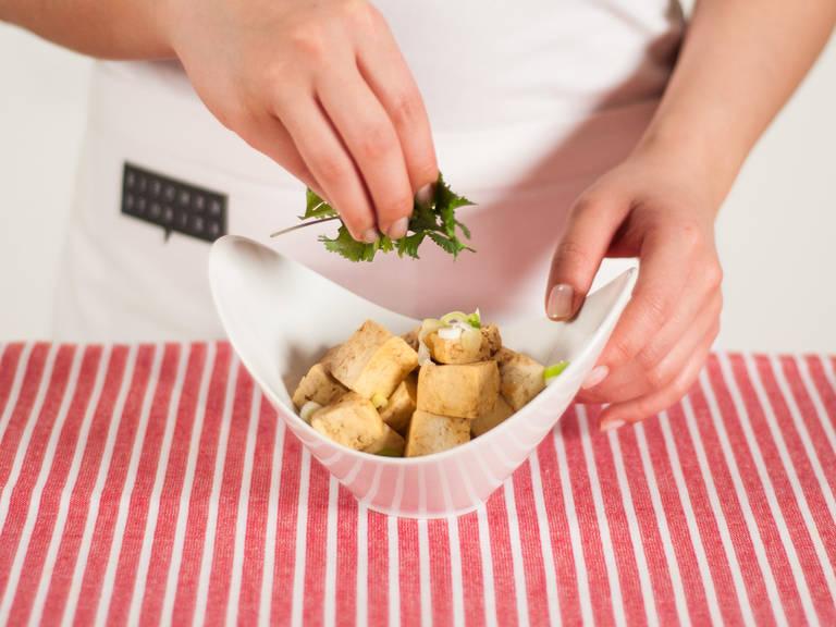 Geschnittene Frühlingszwiebeln und Koriander über den Tofu geben. Mit dem eingelegtem Rettich servieren.